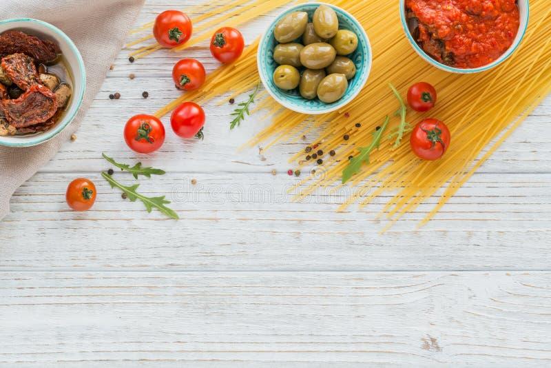 Ingredienti per gli spaghetti della pasta della preparazione - pomodoro, olio d'oliva, spezie, erbe, olive verdi, salsa al pomodo fotografia stock libera da diritti