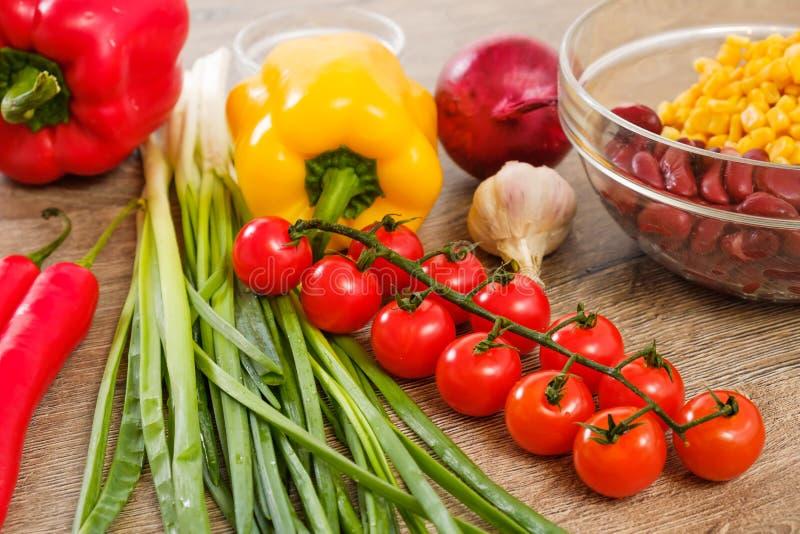 Ingredienti per i Burritos, le verdure, il mais, i pomodori ed i peperoni su fondo di legno Vista superiore immagine stock