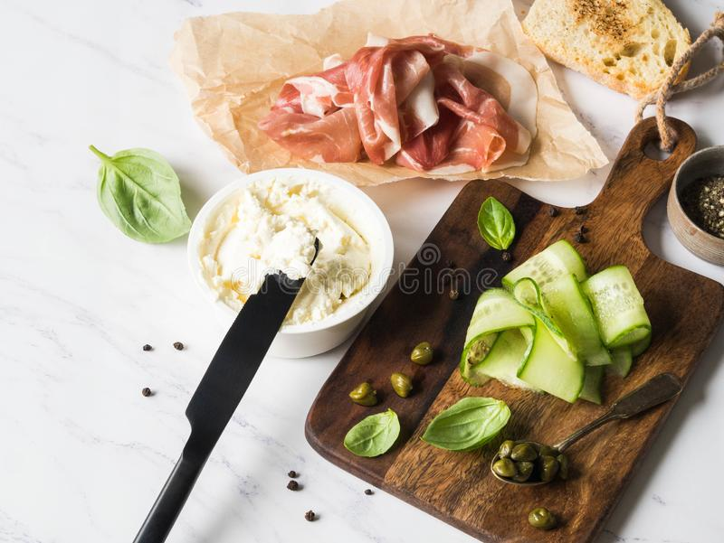 Ingredienti per i panini della preparazione con formaggio cremoso, prosciutto di Parma, fette del cetriolo, capperi, basilico sui immagini stock