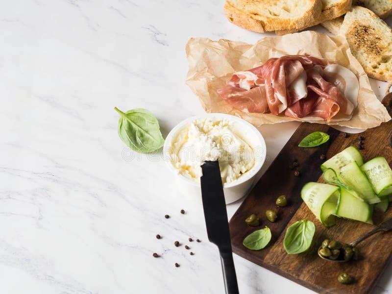 Ingredienti per i panini della preparazione con formaggio cremoso, prosciutto di Parma, fette del cetriolo, capperi, basilico sui immagine stock