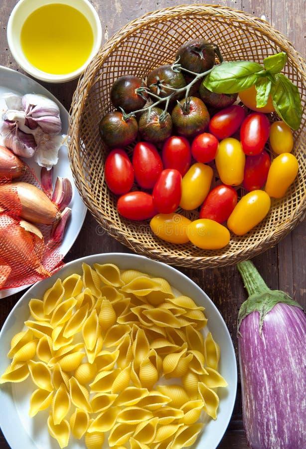 Ingredienti per l'insalata di pasta pomodori variopinti, cipolla, aglio, e fotografia stock