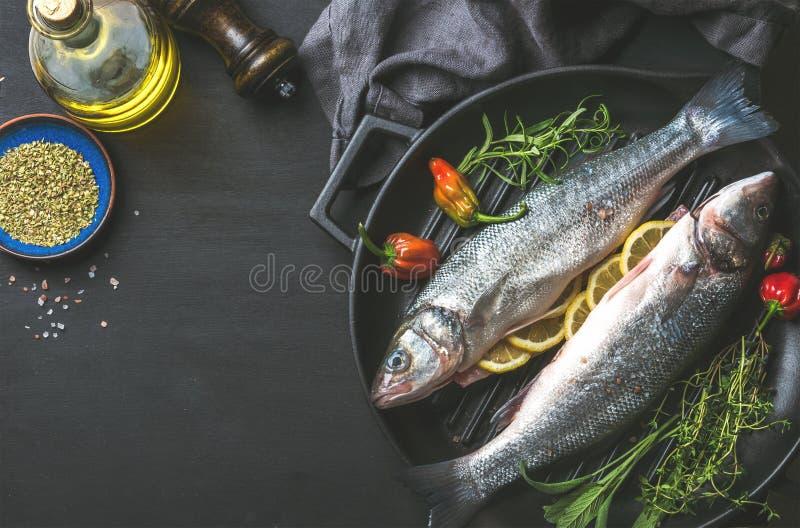 Ingredienti per la cena sana del pesce del cookig Spigola cruda cruda con olio d'oliva, le erbe e le spezie sul grigliare nero fotografia stock libera da diritti