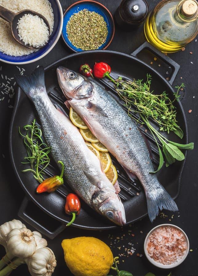 Ingredienti per la cena sana del pesce del cookig Spigola cruda cruda con riso, il limone, l'olio d'oliva, le erbe e le spezie su fotografie stock libere da diritti