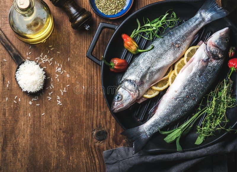 Ingredienti per la cena sana del pesce del cookig Spigola cruda cruda con riso, olio d'oliva, le fette del limone, le erbe e le s fotografie stock libere da diritti