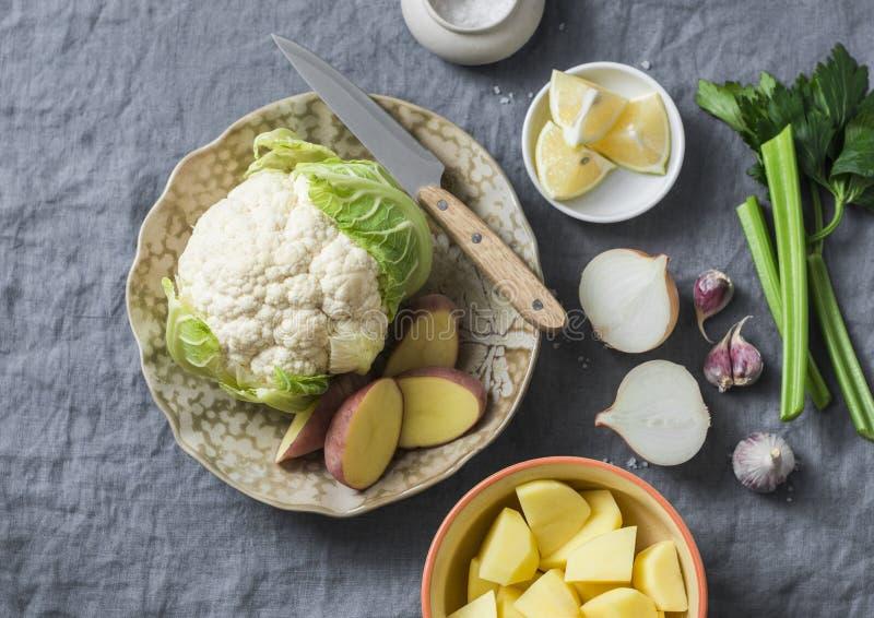Ingredienti per la cottura del purè su un fondo grigio, vista superiore della minestra del cavolfiore della patata Alimento sano  immagine stock