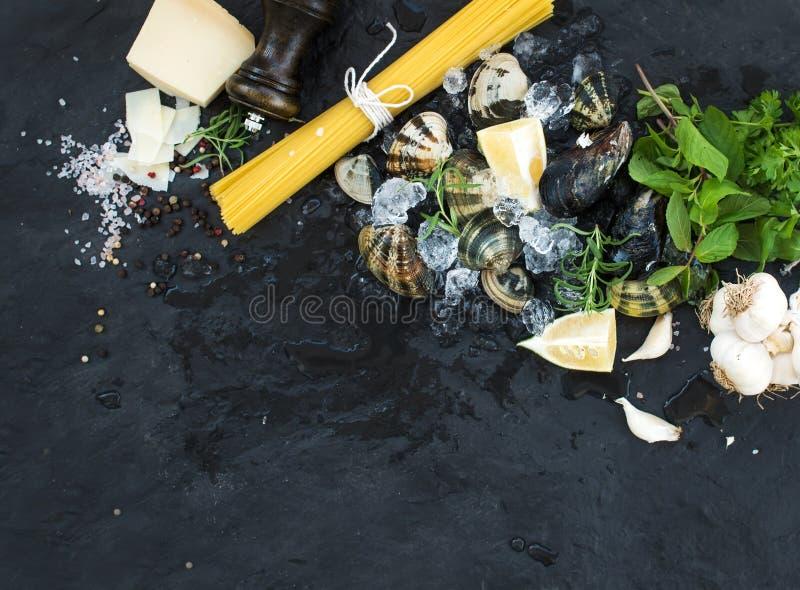 Ingredienti per la cottura del vongole degli spaghetti Vongole su ghiaccio scheggiato, su pasta cruda, su parmigiano, su aglio, s fotografie stock