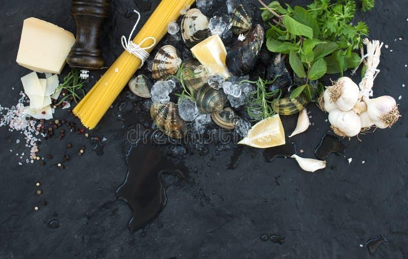 Ingredienti per la cottura del vongole degli spaghetti Vongole su ghiaccio scheggiato, su pasta cruda, su parmigiano, su aglio, s fotografia stock