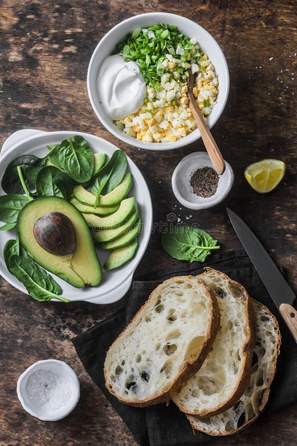 Ingredienti per la cottura dell'avocado, spinaci, insalata dell'uovo sul panino del pane tostato La prima colazione sana dell'ali immagine stock libera da diritti