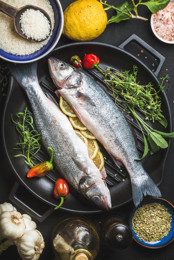 Ingredienti per la cottura della cena sana del pesce Spigola cruda cruda con riso, il limone, le erbe e le spezie sul grigliare n immagine stock libera da diritti