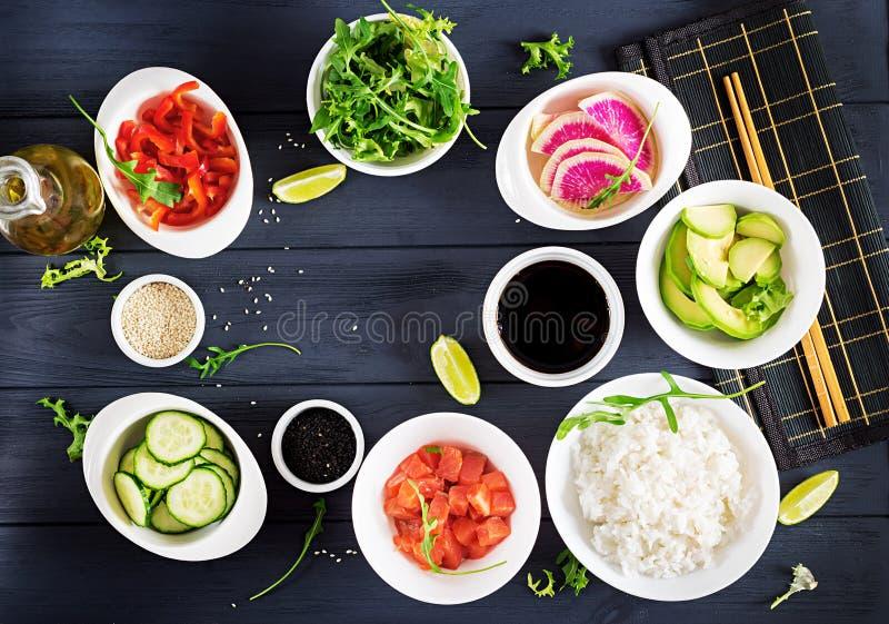 Ingredienti per la cottura della ciotola di color salmone hawaiana del colpo del pesce con riso, l'avocado, la paprica, il cetrio fotografie stock