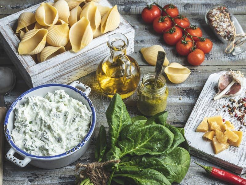 Ingredienti per la cottura della pasta Conchiglioni, foglie degli spinaci, pomodori ciliegia, parmigiano, formaggio cremoso, olio fotografia stock