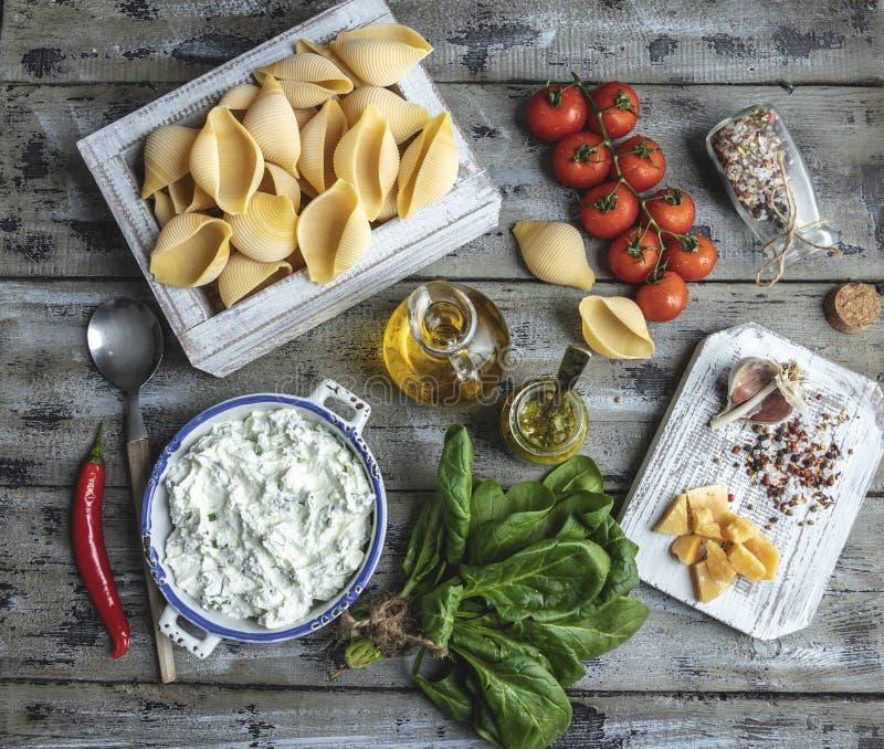 Ingredienti per la cottura della pasta Conchiglioni, foglie degli spinaci, pomodori ciliegia, parmigiano, formaggio cremoso, olio fotografia stock libera da diritti