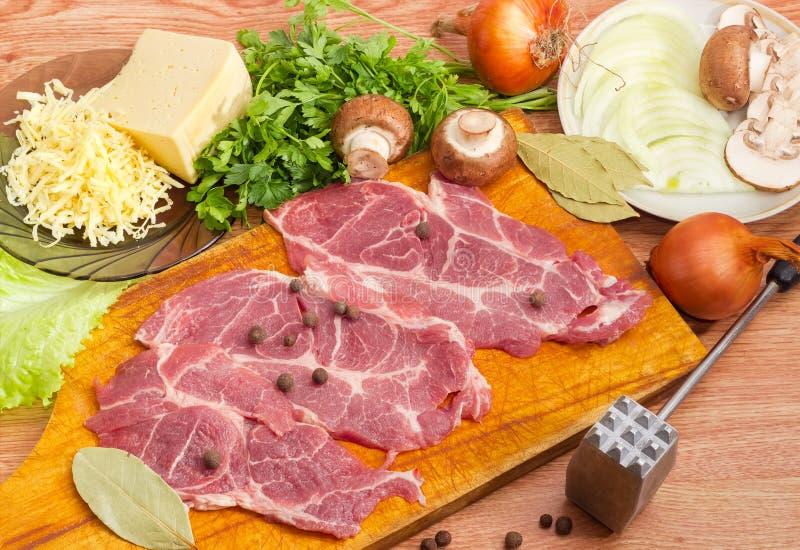 Ingredienti per la cottura delle braciole di maiale al forno con la cipolla, funghi, fotografia stock libera da diritti