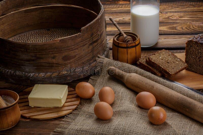Ingredienti per la cottura, le uova, il miele, il pane, la farina ed il latte immagini stock libere da diritti