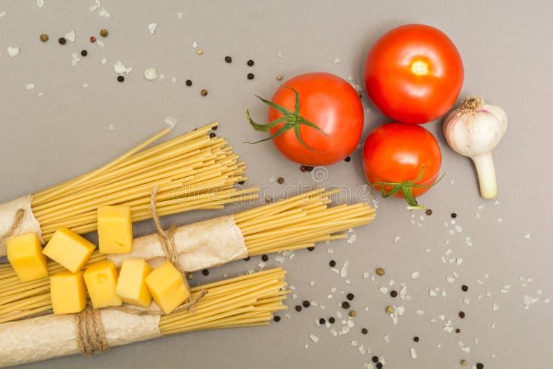 Ingredienti per la preparazione di pasta Spaghetti, formaggio, pomodori, aglio, su un fondo grigio Vista superiore immagine stock