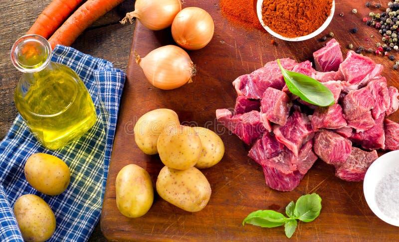 Ingredienti per lo stufato o il goulash sul tagliere anziano fotografie stock