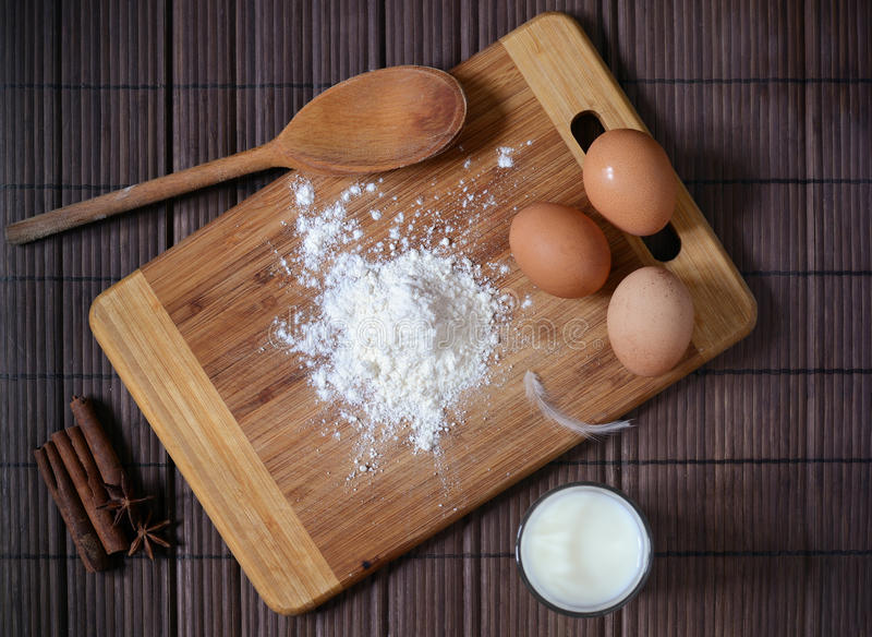 Ingredienti per pane casalingo o pasta Uova, latte, farina su una vista superiore di superficie rustica Fondo della protezione immagine stock