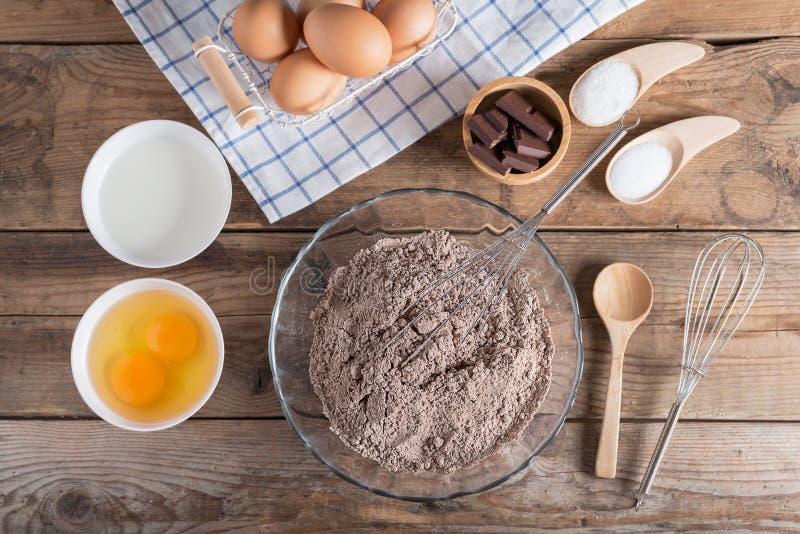 Ingredienti per produrre il cioccolato del dolce su un fondo di legno immagine stock