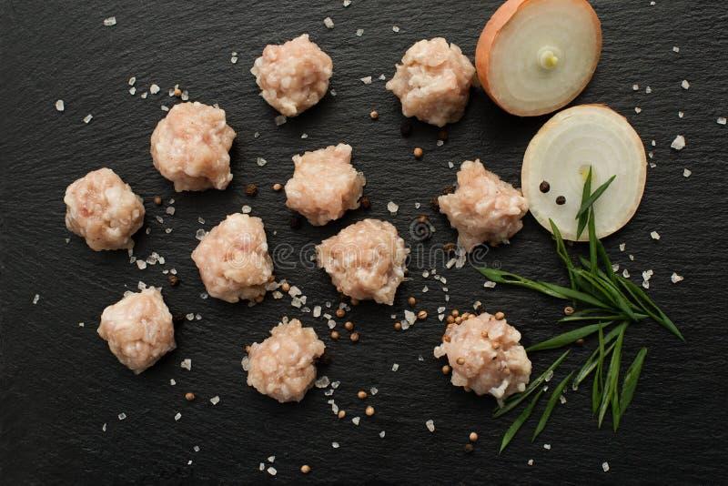 Ingredienti per produrre minestra con le polpette carne cruda, cipolle e tagliatelle su un bordo di pietra nero immagini stock