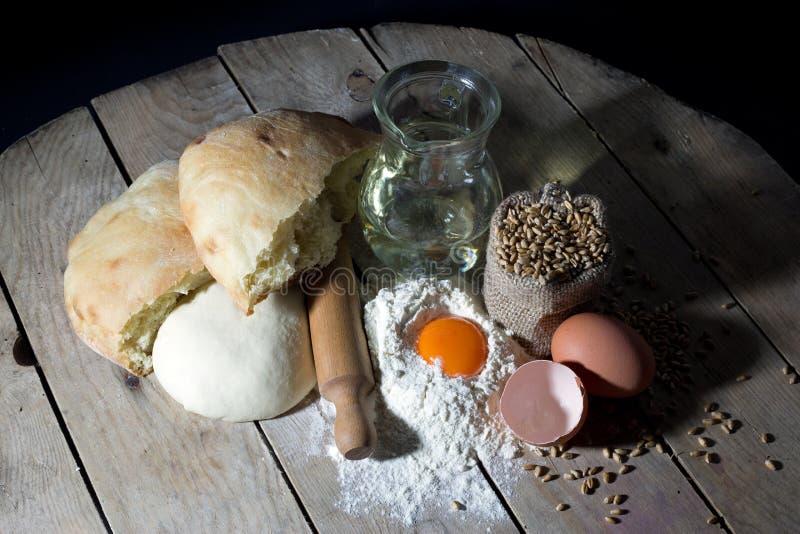 Ingredienti per produrre Pane-farina, Olive Oil, uova con il matterello e la borsa della iuta riempiti di grano sulla Tabella di  immagine stock
