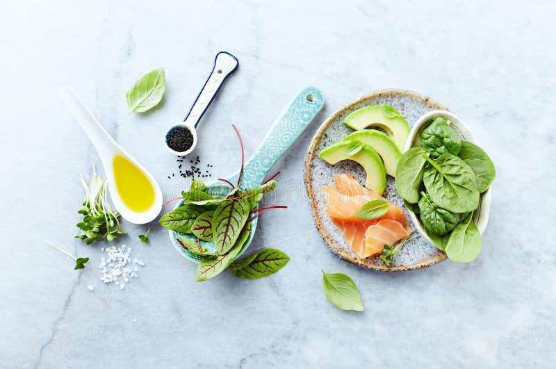 Ingredienti per un'insalata sana su fondo di pietra grigio Il salmone affumicato, avocado, spinaci, acetosa, radis germoglia, cum immagine stock