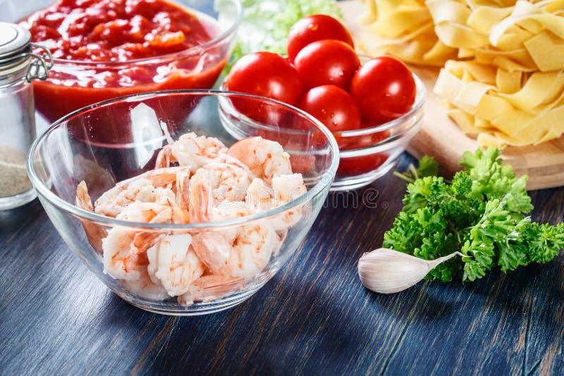 Ingredienti pronti per la preparazione della pasta del pappardelle con gamberetto, i pomodori e le erbe immagini stock