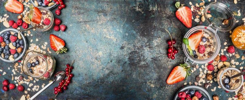 Ingredienti sani della prima colazione Barattoli con i muesli, i dadi e le bacche Faccia colazione con i muesli dei diversi cerea immagini stock libere da diritti