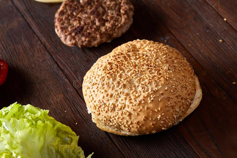 Ingredienti squisiti dell'hamburger artisticamente organizzati sul piatto di legno, primo piano, vista superiore, fuoco selettivo immagine stock