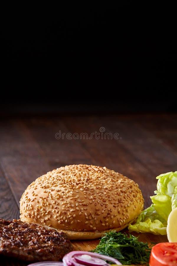 Ingredienti squisiti dell'hamburger artisticamente organizzati sul piatto di legno, primo piano, vista superiore, fuoco selettivo fotografia stock libera da diritti