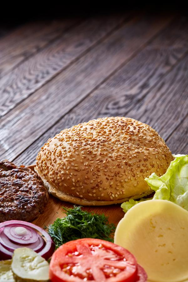 Ingredienti squisiti dell'hamburger artisticamente organizzati sul piatto di legno, primo piano, vista superiore, fuoco selettivo fotografia stock