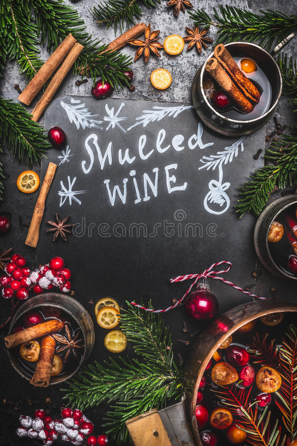 Ingredienti tradizionali del vin brulé con la cottura vaso, le tazze e dei rami dell'abete sul fondo nero della lavagna immagine stock