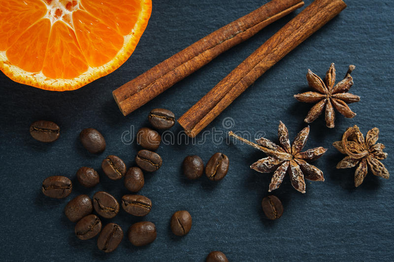 Ingredients: anise star, cinnamon sticks, coffee beans and tangerine. Top view royalty free stock images