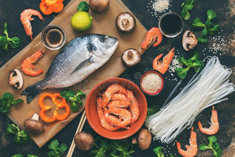 Ingredients for Asian dishes - raw Dorado fish, shrimp, rice noodles,mushrooms, vegetables, dark background, top view. Flat lay, t. Oned photo stock photos