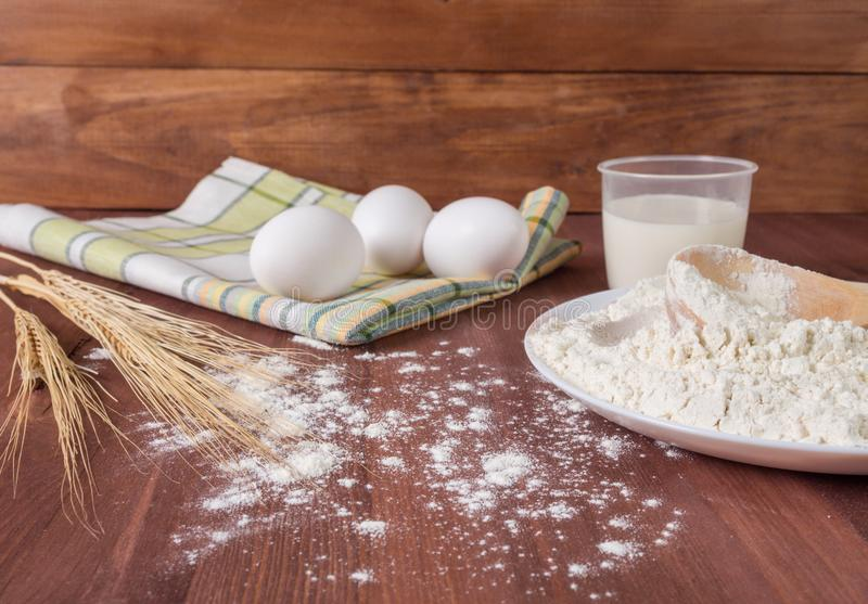 Preparation of the dough. Flour, eggs, milk on a wooden background stock photography