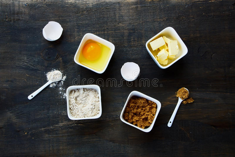 Ingredients. Baking background with eggshell, brown sugar, butter and flour on dark wood. Top view. Food and cuisine ingredients royalty free stock photo