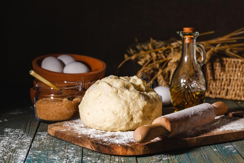Ingredients for baking croissants - flour, wooden spoon, rolling pin, eggs, egg yolks, butter served on wooden background royalty free stock photo