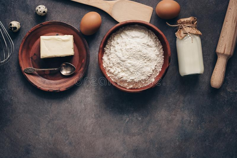 Ingredients for baking on a dark rustic background, flour, butter, eggs, rolling pin, whisk and paddle. Top view, flat lay,copy royalty free stock images