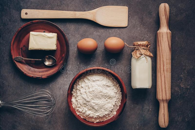 Ingredients for baking on a dark rustic background, flour, butter, eggs, rolling pin, whisk and paddle. Top view, flat lay stock images