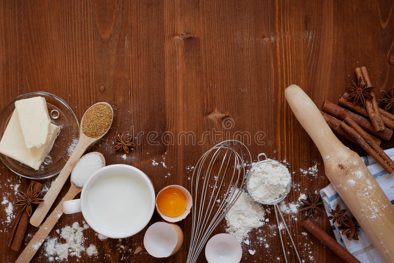Ingredients for baking dough including flour, eggs, milk, butter, sugar, cinnamon, anise star, whisk and rolling pin on wooden royalty free stock image