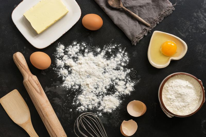 Ingredients for baking, flour, butter, eggs on a black stone background. Top view royalty free stock image