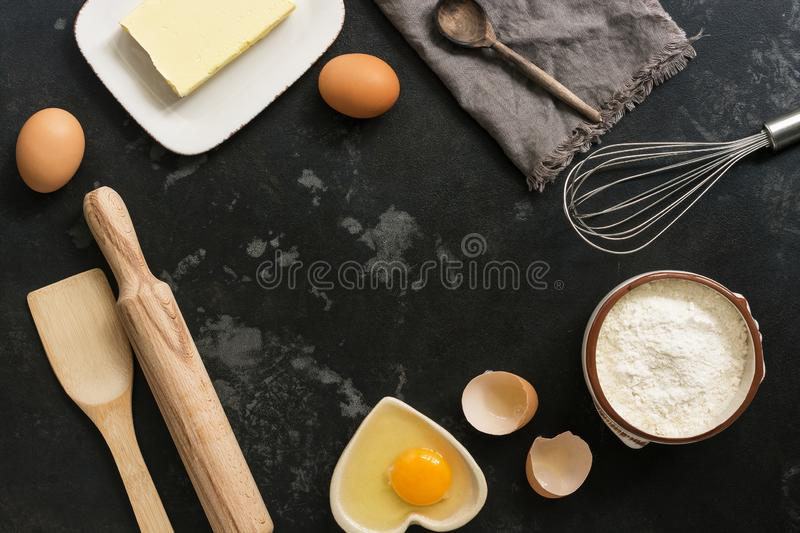 Ingredients for baking, flour, butter, eggs on a black stone background. Top view royalty free stock images