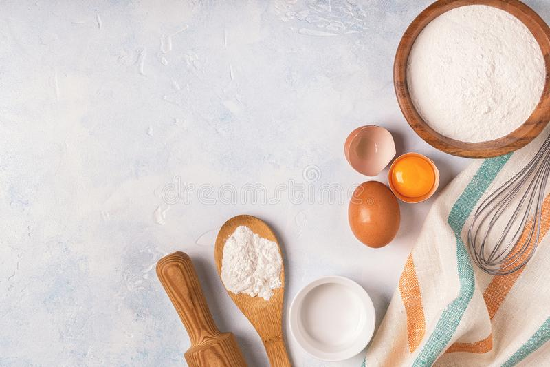 Ingredients for baking - flour, wooden spoon, eggs. royalty free stock image