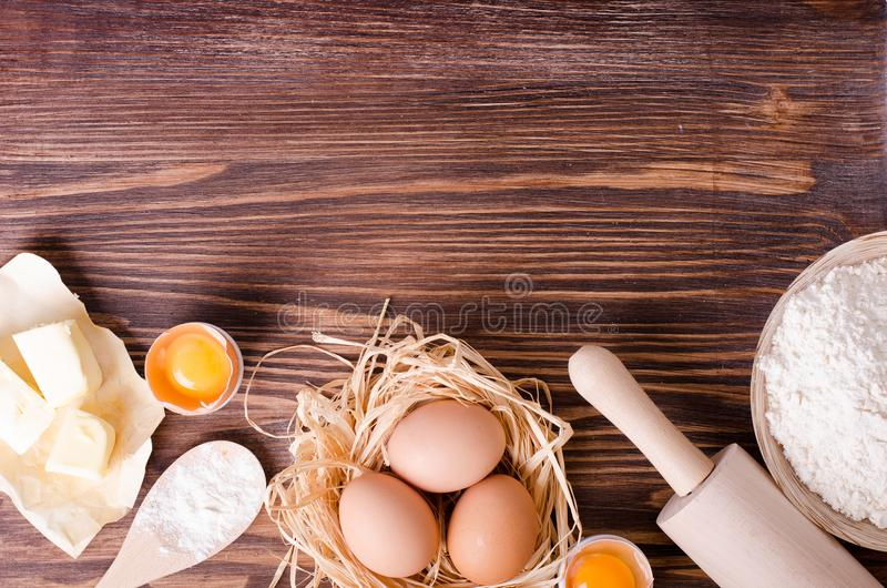 Ingredients for baking - flour, wooden spoon, rolling pin, eggs, egg yolks, butter on vintage wood table from above royalty free stock photography