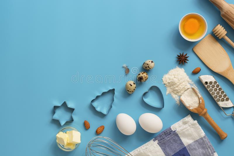 Ingredients for baking and kitchen utensils on a blue background. Top view, flat view, copy space stock photo