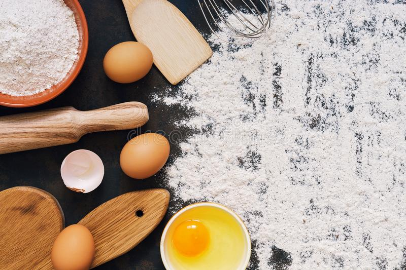 Ingredients for baking rye bread , rye flour, rolling pin, cutting board, eggs, spatula, whisk. Top view, dark rustic background, royalty free stock photo