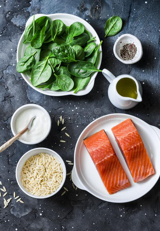 Ingredients for a balanced lunch - salmon fish, spinach, cream, orzo pasta on a dark background, top view royalty free stock photo