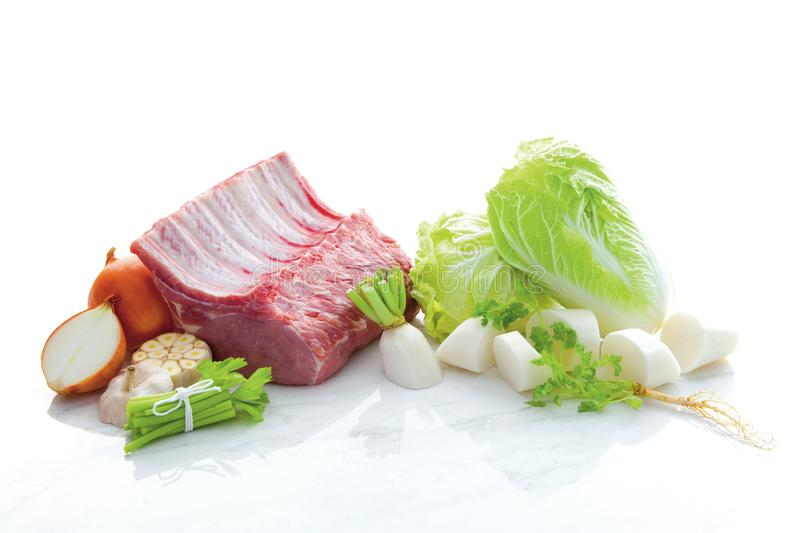 Ingredients for beef soup isolated such as beef, peppers, barbecue, coriander, onion on white marble floor and white background. Ingredients for beef soup stock photo