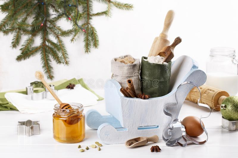 Ingredients for Christmas baking, cookies, gingerbread and cooking utensils for baking. Flour, sugar, egg, honey, rolling pin, cutters, spices on white table stock images