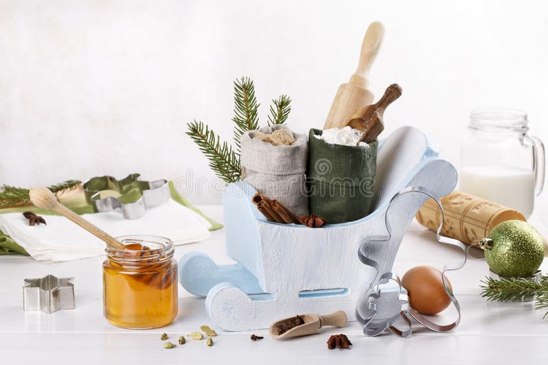 Ingredients for Christmas baking, cookies, gingerbread and cooking utensils for baking. Flour, sugar, egg, honey, rolling pin, cutters, spices on white table stock image