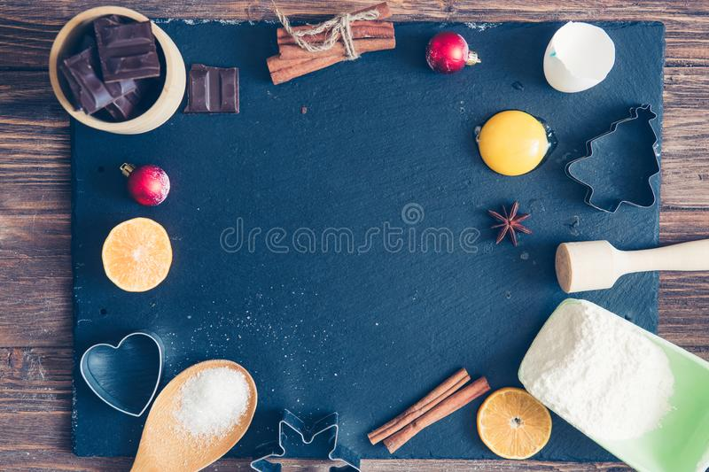 Ingredients for Christmas, winter baking cookies. Flour, cranberries, dried oranges, cinnamon, spices on a black stone table, top stock photos